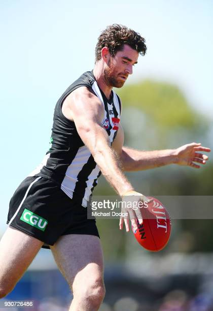 Tyson Goldsack of the Magpies and Marcus Adams of the Bulldogs compete for the ball kicks the ball during the JLT Community Series AFL match between...