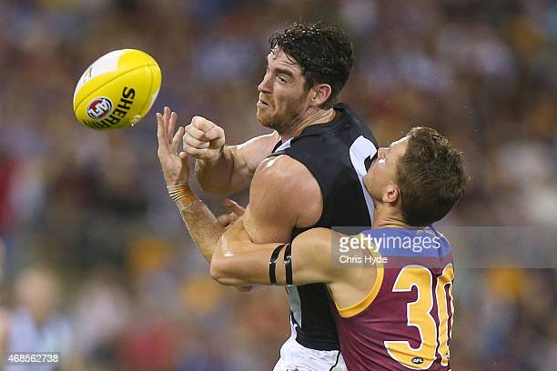 Tyson Goldsack of the Magpies handballs while tackled by Jack Redden of the Lions during the round one AFL match between the Brisbane Lions and...