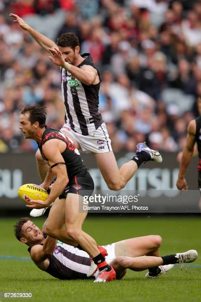 Tyson Goldsack of the Magpies jumps over team mate Jeremy Howe to chase Travis Colyer of the Bombers during the round five AFL match between the...