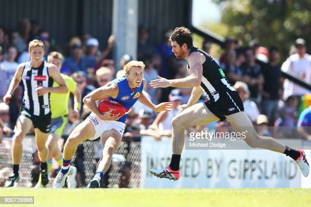 Tyson Goldsack of the Magpies tries to tackle Bailey Dale of the Bulldogs during the JLT Community Series AFL match between Collingwood Magpies and...
