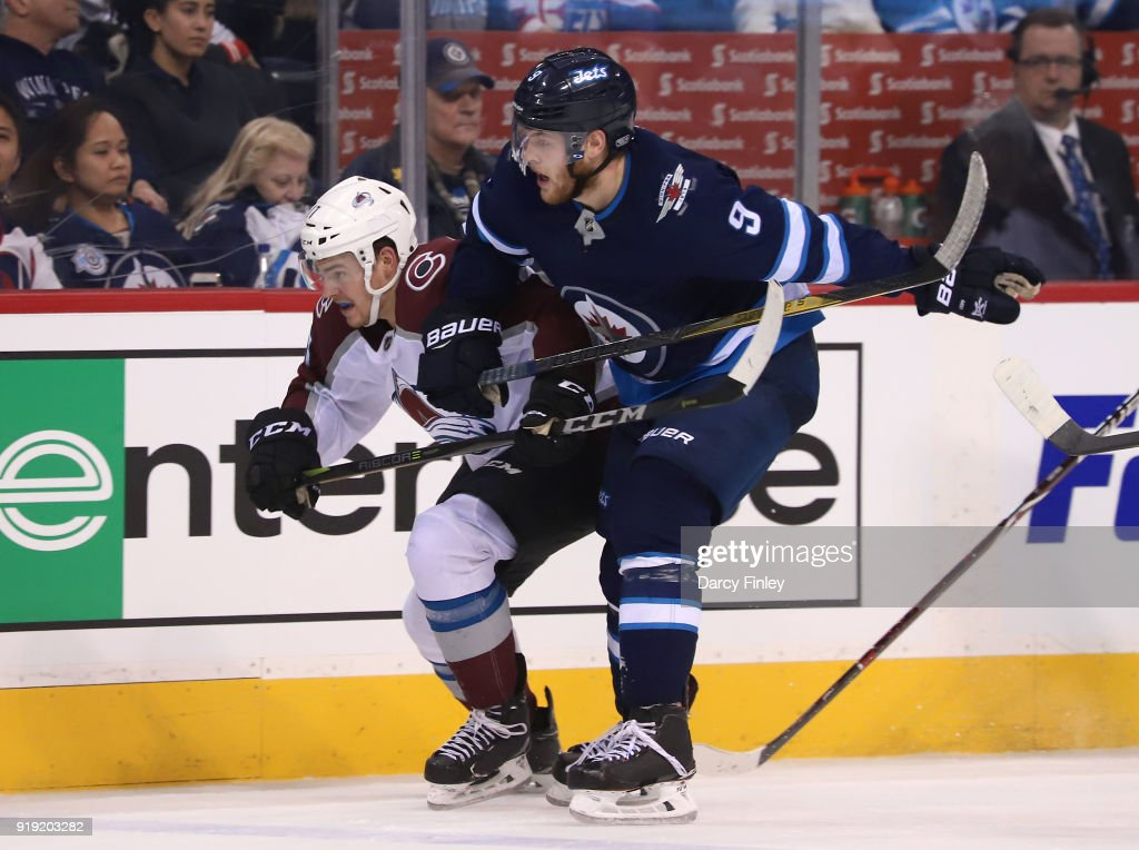 Tyson Jost #17 of the Colorado Avalanche and Andrew Copp #9 of the Winnipeg Jets follow the play down the ice during third period action at the Bell MTS Place on February 16, 2018 in Winnipeg, Manitoba, Canada.