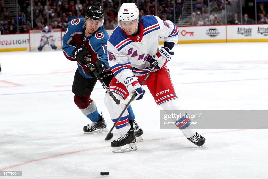 Tyson Jost #17 of the Colorado Avalanche fights for the puck against Vinni Lettieri #95 of the New York Rangers at the Pepsi Center on January 20, 2018 in Denver, Colorado.