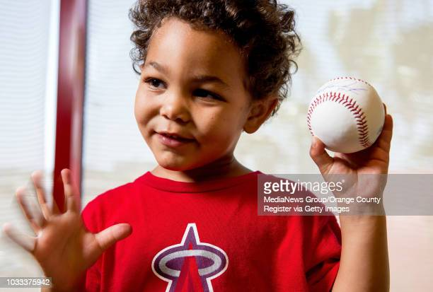 Tyson Kendrick son of Angel Howie Kendrick holds a baseball signed by his dad The signed baseballs will be part of a fundraiser on Saturday June 21...