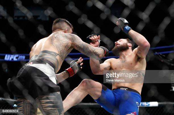 Tyson Pedro of Australia connects with a punch that knocks down Paul Craig of Scotland in a light heavyweight bout during UFC 209 at TMobile Arena on...