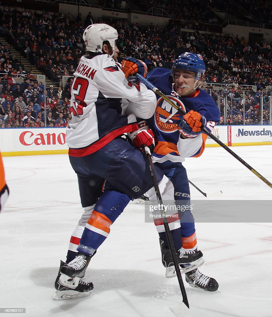 Tyson Strachan #23 of the Washington Capitals is hit by Anders Lee #27 of the New York Islanders during the second period at the Nassau Veterans Memorial Coliseum on April 5, 2014 in Uniondale, New York.