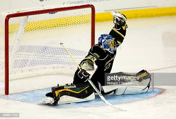 Tyson Teichmann of the St. Thomas University Tommies makes a glove save against the Massachusetts Lowell River Hawks during NCAA exhibition hockey at...
