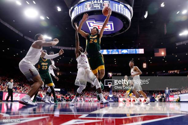 Tyson Ward of the North Dakota State Bison shoots over Dylan Smith and Ira Lee of the Arizona Wildcats during the first half of the college...