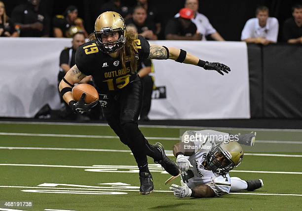 Tysson Poots of the Las Vegas Outlaws escapes a tackle by Virgil Gray of the San Jose SaberCats to score a touchdown during the Outlaws' inaugural...