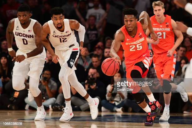 Tyus Battle of the Syracuse Orange dribbles down the court while teammate Marek Dolezaj and Connecticut Huskies players Eric Cobb and Tyler Polley...