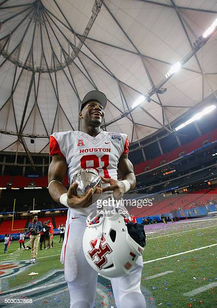 Tyus Bowser of the Houston Cougars celebrates with the trophy after their 3824 win over the Florida State Seminoles during the ChickfilA Peach Bowl...