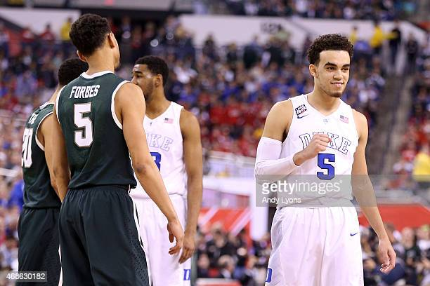 Tyus Jones of the Duke Blue Devils reacts after defeating the Michigan State Spartans as Bryn Forbes looks on during the NCAA Men's Final Four...