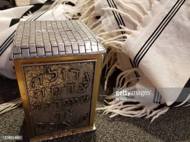 tzedaqa/ donation box and jewish prayer shawl / tallit - jewish prayer shawl stock pictures, royalty-free photos & images