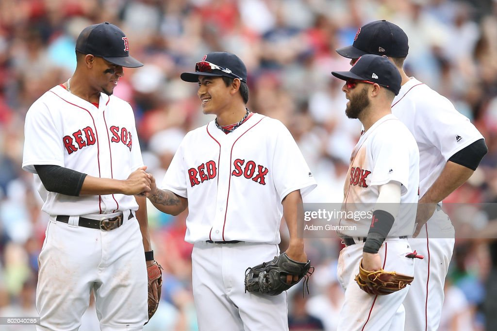 Tzu-Wei Lin #73 of the Boston Red Sox is congratulated by teammates after making a bare-handed catch and throw in the eighth inning of a game against the Los Angeles Angels of Anaheim at Fenway Park on June 25, 2017 in Boston, Massachusetts.
