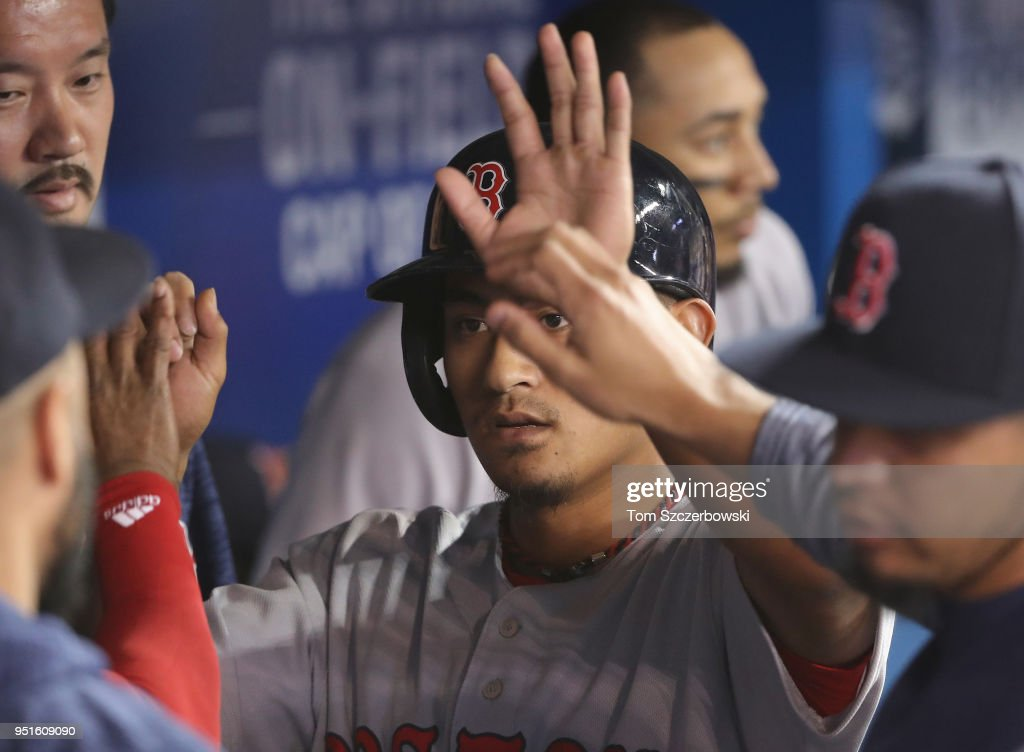 Tzu-Wei Lin #5 of the Boston Red Sox is congratulated by teammates in the dugout after scoring a run in the third inning during MLB game action against the Toronto Blue Jays at Rogers Centre on April 26, 2018 in Toronto, Canada.