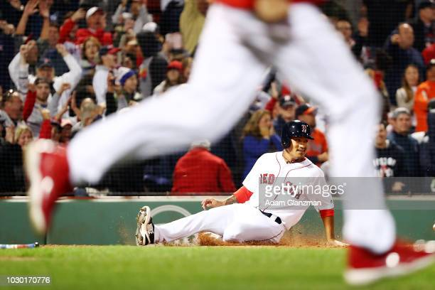 TzuWei Lin of the Boston Red Sox slides into home plate to score the gamewinning run as his teammates rush the field after Mitch Moreland of the...