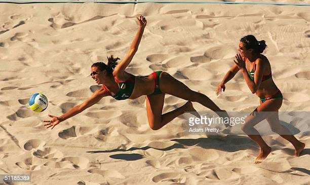 Tzvetelina Yanchulova of Bulagria dives for the ball while teammate and sister Petia Yanchulova looks on during the women's preliminary match between...