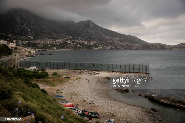 U2010 MAY 19: Spanish troops guard the Tarajal beach on the border between Spain and Morocco while cleaning workers remove the dirt accumulated all...
