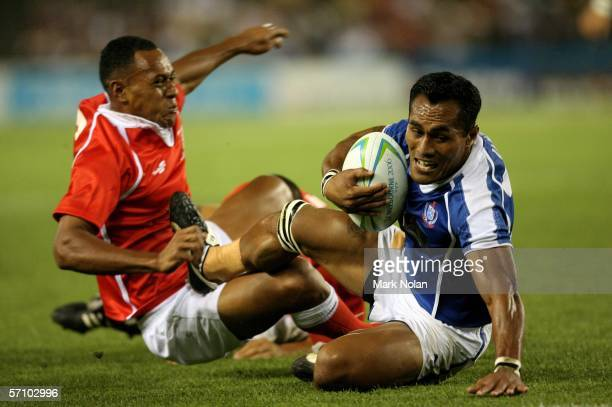 Uale Mai of Samoa shrugs of the tackle from Vungakoto Lilo of Tonga to score a try during the rugby sevens match between Samoa and Tonga at the...