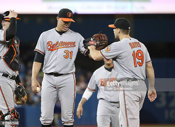 Ubaldo Jimenez of the Baltimore Orioles is congratulated by Chris Davis moments before being relieved in the seventh inning during MLB game action...