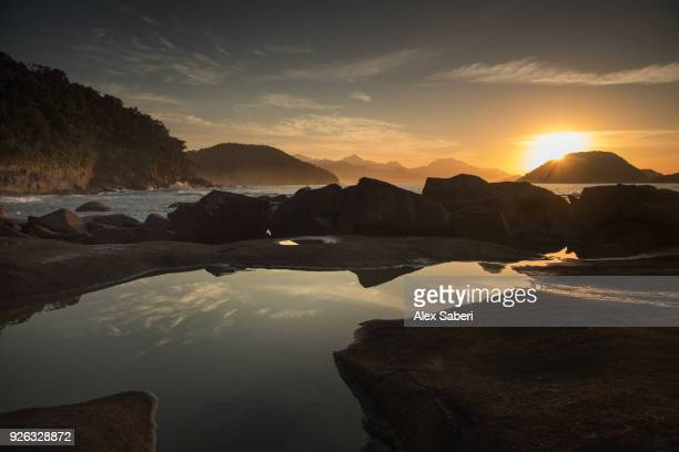 Rocks and reflections on Praia das Conchas beach at sunset.