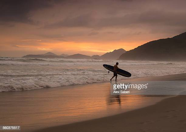 A surfer makes his way out of the water at sunset in Itamambuca, Ubatuba, Brazil.