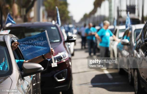 Uber and Lyft drivers line up in their vehicles before driving in a rolling march as part of a pro-union march through a section of Los Angeles...