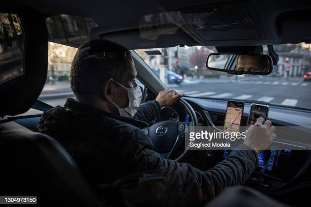 Uber driver checks his phone as he drives on February 27, 2021 in Paris, France. Despite the development of Covid-19 vaccine campaigns to prevent...