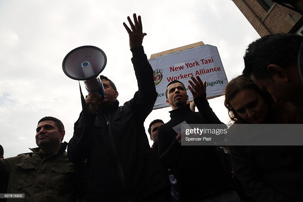 Uber driver representitives speak to hundreds of Uber drivers as they protest the company's recent fare cuts and went on strike in front of the car service's New York offices on February 1, 2016 in New York City. The drivers say Uber continues to cut into their earnings without cutting into its own take from each ride. In claiming fare reduction would mean more work for drivers, the San Francisco based company cut its prices by 15 percent last week.