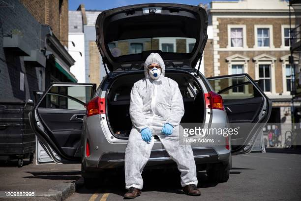 Uber driver Yasar Gorur wears personal protective equipment while cleaning his vehicle on April 14, 2020 in London, United Kingdom. Gorur says he...