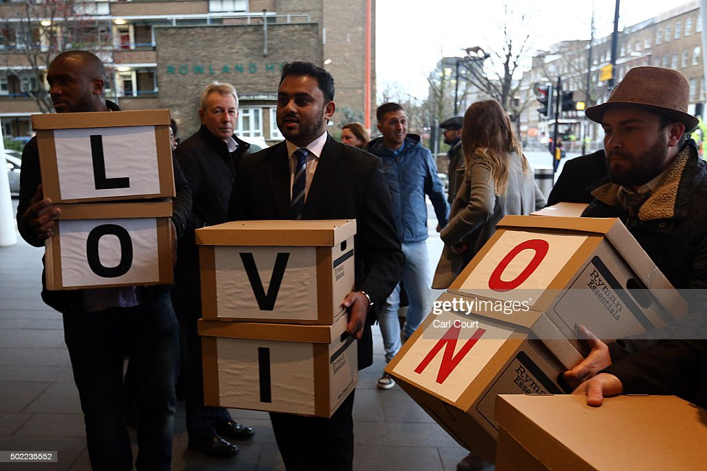 Uber drivers carry boxes of petitions before posing for a photograph outside the Transport for London headquarters on December 22, 2015 in London, England. The Uber drivers formally handed in the petition, signed by over 205,000 people, to oppose proposals such as introducing minimum 5 minute waiting times.
