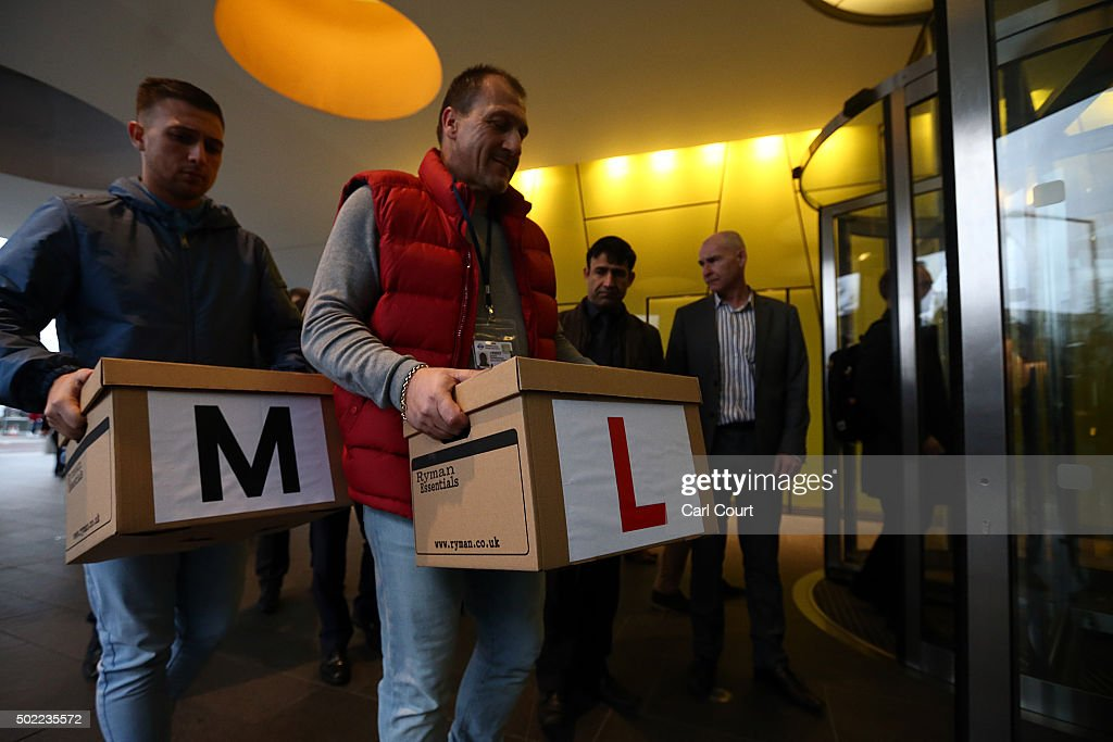Uber drivers carry boxes of petitions into the Transport for London headquarters on December 22, 2015 in London, England. The Uber drivers formally handed in the petition, signed by over 205,000 people, to oppose proposals such as introducing minimum 5 minute waiting times.