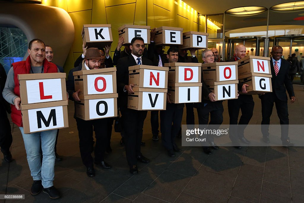 Uber drivers pose for a photograph with boxes of petitions outside the Transport for London headquarters on December 22, 2015 in London, England. The Uber drivers formally handed in the petition, signed by over 205,000 people, to oppose proposals such as introducing minimum 5 minute waiting times.