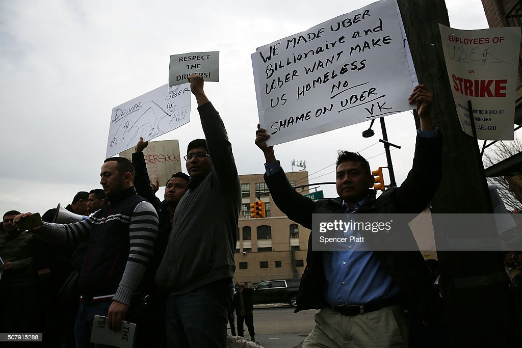 Uber drivers protest the company's recent fare cuts and go on strike in front of the car service's New York offices on February 1, 2016 in New York City. The drivers say Uber continues to cut into their earnings without cutting into its own take from each ride. In claiming fare reduction would mean more work for drivers, the San Francisco based company cut its prices by 15 percent last week.