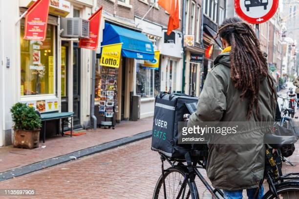 uber eats delivery man on a bicycle in amsterdam - commercial activity stock pictures, royalty-free photos & images