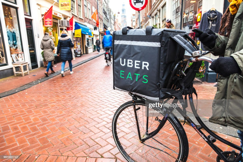Uber Eats delivery man on a bicycle in Amsterdam : Stock Photo