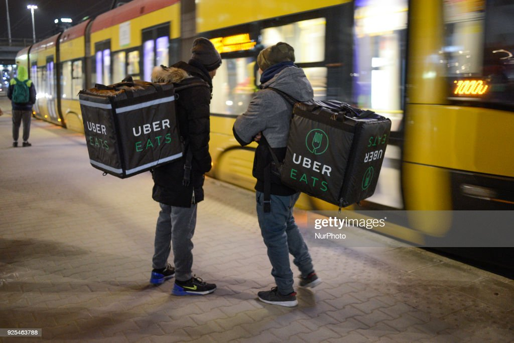 Uber Eats delivery workers are seen waiting for a tram in central Warsaw, Poland on February 27, 2018.