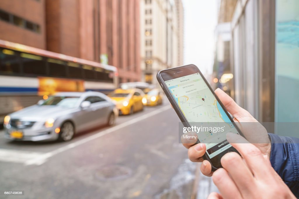 NYC Uber Taxi Chauffeur Call On Apple iPhone New York City Taxi Cab : Stock Photo