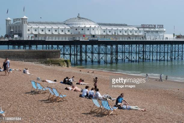 UBrighton, East Sussex, UK, 21/5/10. The pebbly beach by the seaside, with sunbathers, beach chairs and a view of the pier, Brighton, East Sussex,...