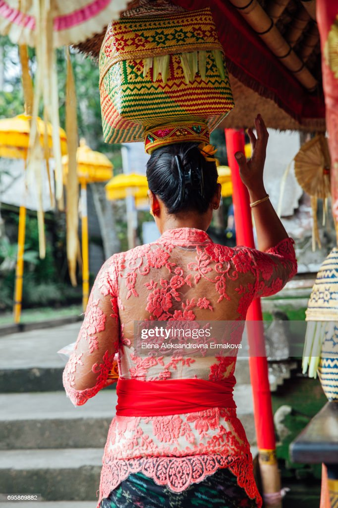 EDITORIAL: Ubud, Indonesia -March 02, 2016: Balinese woman in traditional clothes  carrying ceremonial box with offerings on her head during Balinese New Year or Nyepi Day celebrations : Stock Photo