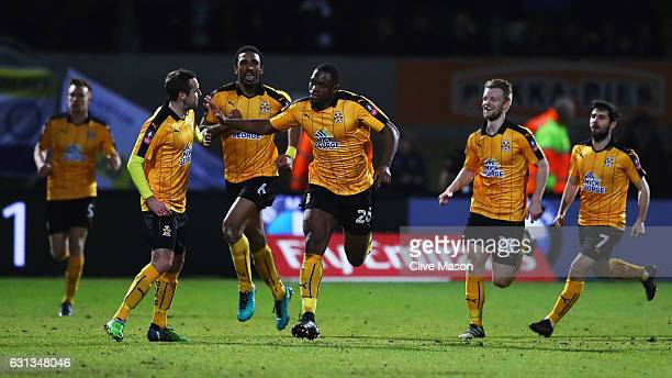 Uche Ikpeazu of Cambridge United celebrates with team mates as he scores their first goal during the Emirates FA Cup Third Round match between...