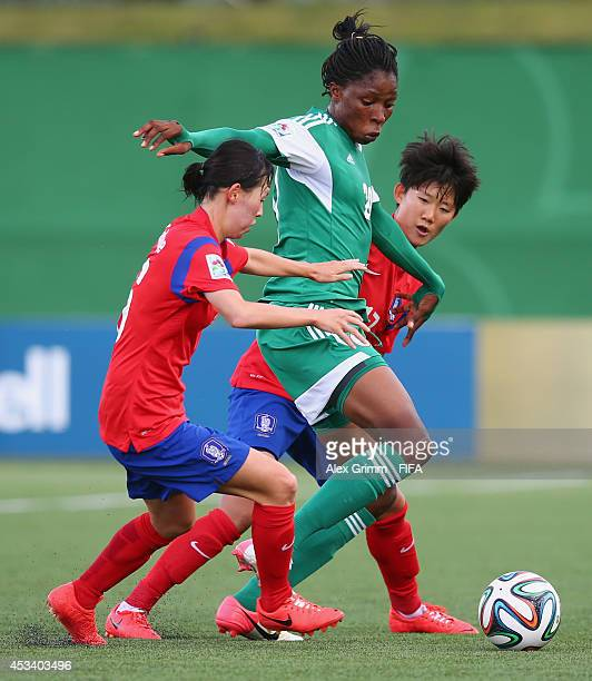 Uchechi Sunday of Nigeria is challenged by Ha Eunhye and Kim Hyeyeong of Korea Republic during the FIFA U20 Women's World Cup Canada 2014 group C...