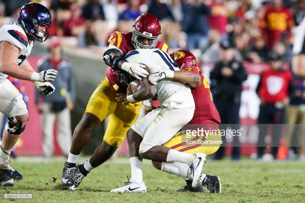 Uchenna Nwosu of the USC Trojans and Malik Dorton of the USC Trojans apply pressure on Khalil Tate of the Arizona Wildcats during a college football...