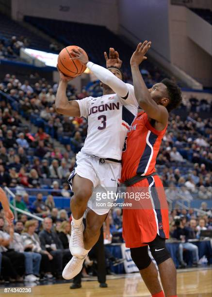 UConn Huskies Guard Alterique Gilbert drives to the basket while defended by Stony Brook Seawolves Forward Anthony Ochefu during the game as the...