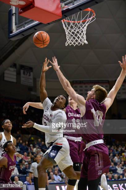 UConn Huskies Guard Alterique Gilbert makes his way to the basket while defended by Colgate Raiders Guard Jack Ferguson and Colgate Raiders Forward...