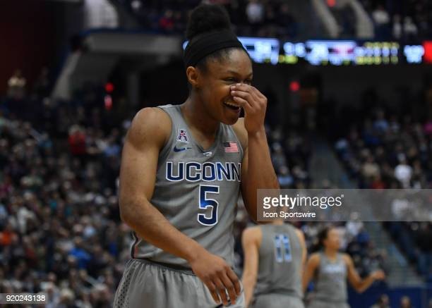 UConn Huskies Guard Crystal Dangerfield trys to hold back her laughter after an errant play during the game as the UConn Huskies host the Temple Owls...