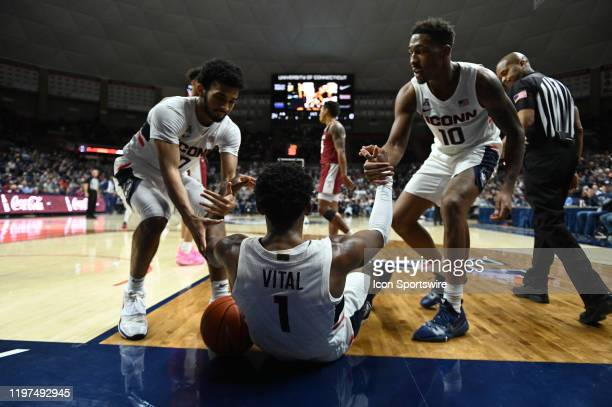 UConn Huskies guard Jalen Gaffney and UConn Huskies guard Brendan Adams help UConn Huskies guard Christian Vital off of the ground during the game as...