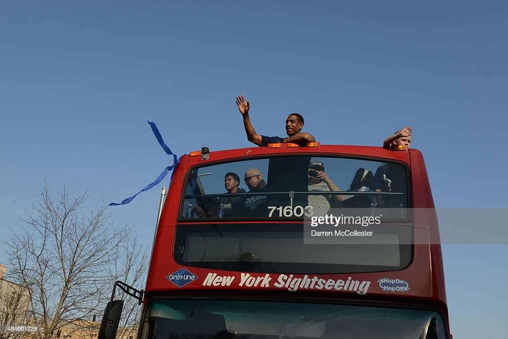 Uconn Huskies head coach Kevin Ollie and his team ride in a victory parade to celebrate their national championship April 13, 2014 in Hartford, Connecticut. This year was the second time both the men's and women's Uconn basketball teams have won national championships in the same year.