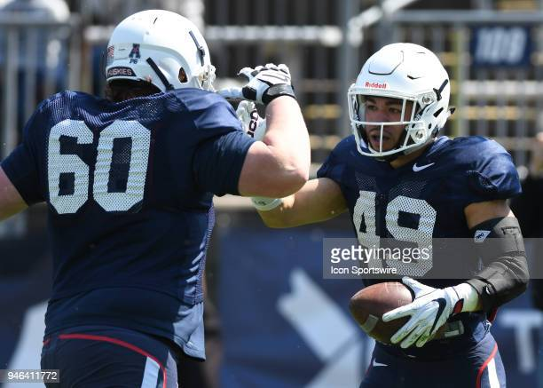 UConn Huskies offensive lineman Ben Bonvicini and UConn Huskies running back Donevin O'Reilly celebrate after scoring a touchdown during the UConn...