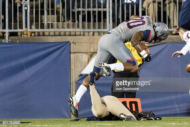 UConn Safety Obi Melifonwu hurdles a camera girl on the sidelines after an interception during the second quarter of a NCAA football game between the...