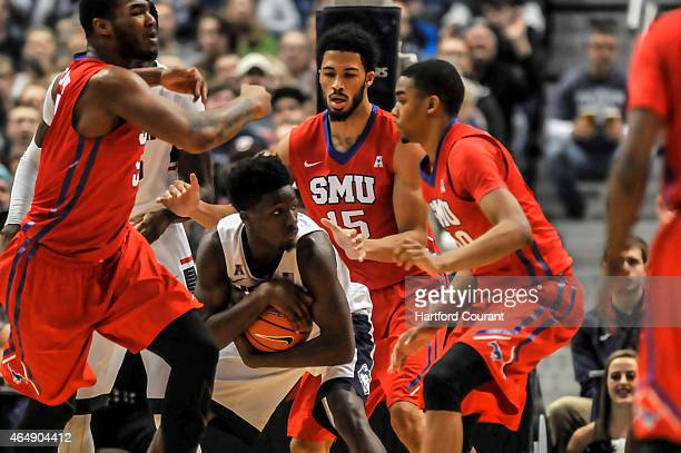 UConn's Daniel Hamilton protects a defensive rebound from Southern Methodist's Cannen Cunningham after UConn's defense jammed up a shot attempt by...